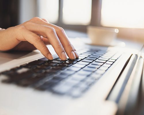 Close-up of human hand on laptop keyboard